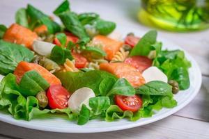 närbild av sallad med färska grönsaker och lax