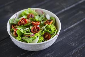 sallad med färska grönsaker, trädgårdsörter och soltorkade tomater foto