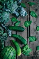 olika gröna grönsaker på träbord foto