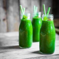 färsk grön smoothie på rustik träbakgrund foto