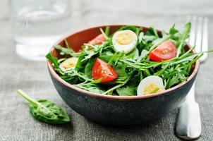 sallad med rucola, spenat, tomater och ägg. foto
