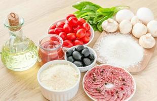 ingredienser för pizza på träbakgrunden foto