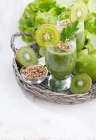 frisk grön smoothie med groddar och vit träbakgrund foto