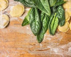 rå tortellini med gröna spenatsblad på träbakgrund foto