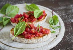 bruschetta med tomater och färsk spenat foto