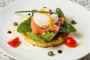 pocherat ägg med lax, tomat och spenat foto
