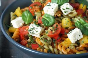 italiensk pasta med färska osttomater och spenat foto