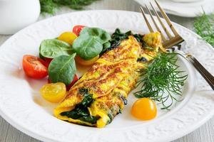 omelett med spenat och salladtomat. foto