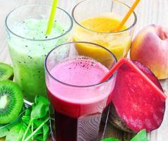 färska detoxjuicer med rödbetor, persikor, spenat och kiwi foto