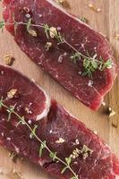 rått nötkött av svin med kryddor över träbord foto