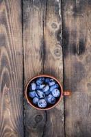 plommon i kopp på träbakgrund foto