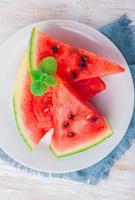 skivad vattenmelon med myntablad på en vit platta foto