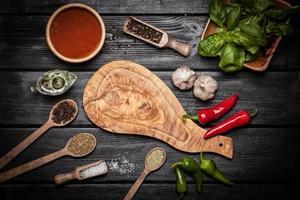 olivträskiva med olika kryddor foto