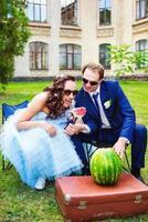 bruden och brudgummen äter vattenmelon på picknicken foto