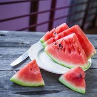 skivor vattenmelon på en tallrik på en träbakgrund foto