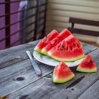 skivor vattenmelon och en kniv på en tallrik foto