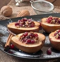 bakade päron med tranbär, honung och valnötter foto