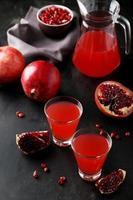 granatäpplesaft i glas och kanna på svart bakgrund foto