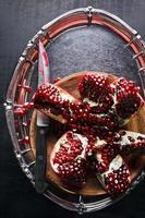 skär granatäpple på ett silverbricka och en kniv foto