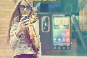 kvinna på gatan med smartphone foto