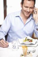 affärsman på mobiltelefon i café foto