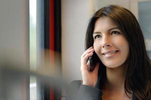 leende kvinna med mobiltelefon foto