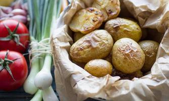 bakade potatis med vitlök och färska grönsaker foto