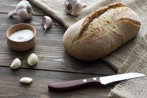 vitlök, salt, bröd och en kniv foto