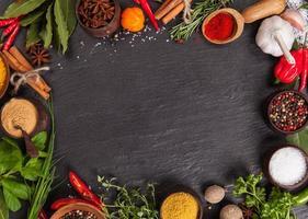 olika kryddor på svart sten foto