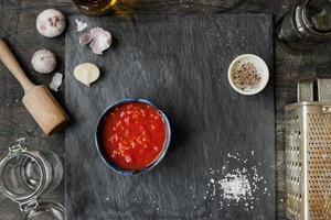 pureade tomater i en keramisk maträtt på ett bord foto