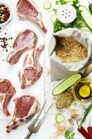 rå lammkotletter och brunt ris foto