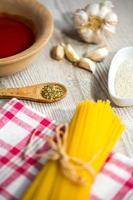 spaghetti och andra ingredienser, parmesan, oregano på köksbordet