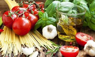italienska matlagningsingredienser, spaghetti, tomates, olivolja och bas foto