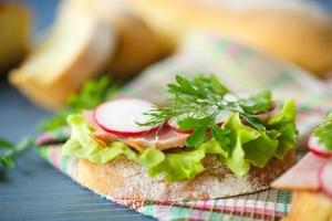 smörgås med sallad, skinka och rädisor foto