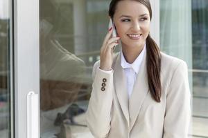 glad affärskvinna med mobiltelefon foto
