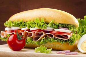 stor smörgås med skinka, ost och grönsaker foto