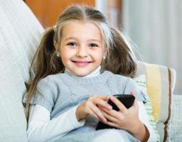 liten flicka med mobiltelefon inomhus foto