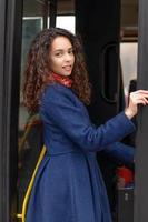 kvinna kommer in i dörren till bussen foto