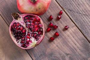 halv granatäpple på träbord foto