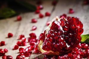 färska skalade granatäpplen med rubinröda frön foto