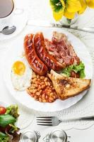 full engelsk frukost med bacon, korv, stekt ägg och bakat