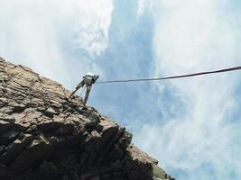 bergsklättrare som rappellerar ner bergsytan foto