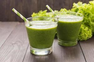 friska gröna grönsaker och grön fruktsmoothie på rustikt trä foto