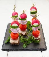 förrätt med sill, rågbröd och grönsaker på spett foto