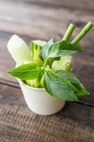 närbild grönsaksmat och kopp på träbord foto
