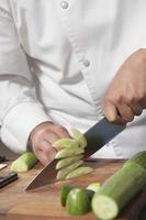 kock som skivar gurka på skärbräda foto