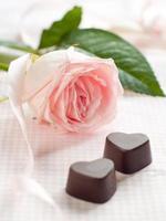 rosa ros med chokladgodis foto