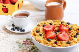 frukost - cornflakes med jordgubbar och blåbär foto