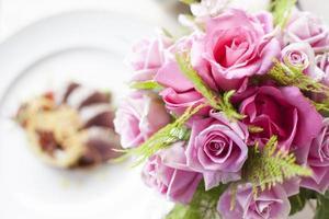 rosa rosblomma framför nötköttmedaljonger