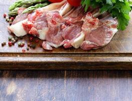 rått kött, lammkotletter med grönsaker på träplatta foto